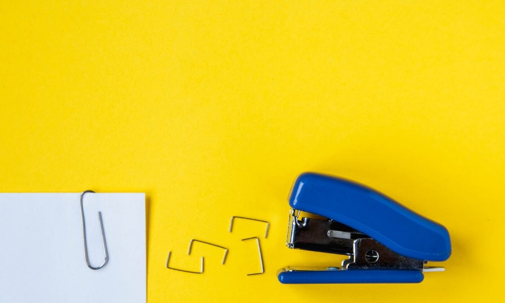 A stapler, staples, and a document with a paper clip with a yellow background.
